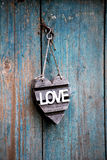 Hearted shaped Love sign hanging on an old door. Hearted shaped Love sign hanging on an old weathered wooden door with peeling blue paint conceptual of Royalty Free Stock Photography