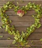 Heartframe丝毫老木地板和秋叶落和花 免版税库存照片
