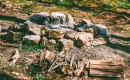 Hearth for a fire folded of stones and dry firewood in the forest royalty free stock image