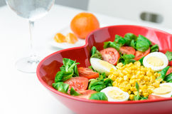 Hearth shape salad. Simple and healthy salad made ​with lettuce, tomatoes, eggs, corn and olive oil.  Served on a plate with a heart shape Stock Photo