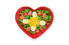 Hearth shape salad. Simple and healthy salad made ​with lettuce, tomatoes, eggs, corn and olive oil.  Served on a plate with a heart shape Stock Images