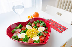 Hearth shape salad. Simple and healthy salad made ​with lettuce, tomatoes, eggs, corn and olive oil.  Served on a plate with a heart shape Royalty Free Stock Image