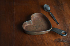 Hearth shaped cast iron  saucepan with silver tea spoon on wood Royalty Free Stock Photography