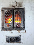 The hearth. White stove with a burning fireplace stock image