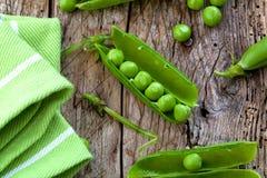 Горохи и стручки Hearthy свежие зеленые на деревенской деревянной предпосылке стоковое фото