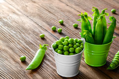 Hearthy fresh green peas and pods in a bucket on Royalty Free Stock Image