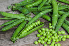 Hearthy fresh green peas and pods on rustic fabric background Royalty Free Stock Images