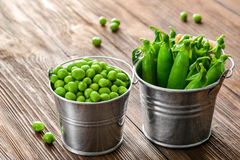 Hearthy fresh green peas and pods on rustic wood Royalty Free Stock Images