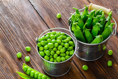 Hearthy fresh green peas and pods on rustic wood Stock Photography