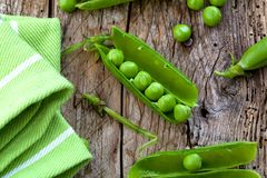 Hearthy fresh green peas and pods on rustic wooden background. stock photo