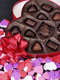 Hearts 042. Multi colored heart cut outs spilled around a heart shaped box of chocolate candy. A shiny red bow completes the setting Stock Images
