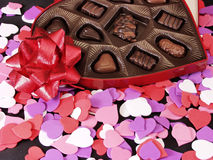 Hearts 047. Multi colored heart cut outs spilled around a heart shaped box of chocolate candy. A shiny red bow completes the setting Royalty Free Stock Image