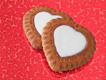 Hearts. Two heart-like biscuits over red metallic background Royalty Free Stock Image