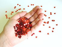 Hearts. Many of red sequin hearts in a hand royalty free stock photo