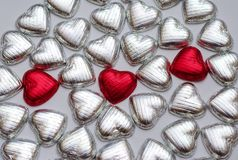 Hearts. Three red chocolate hearts in a sea of silver hearts Stock Photos