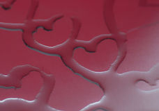 Hearts. Hart formed by water on a metal surface reflecting  in red Stock Images