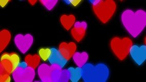 Hearts background animation. Colorful hearts slowly falling down on a dark background with particles flowing around.  stock video