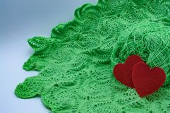 Hearts on the background of a knitted pattern green threads made by the hands of love royalty free stock photo