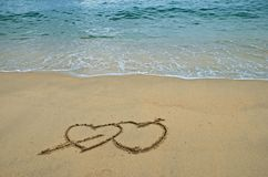Hearts in the beach. 2 Hearts drawn on the surfy beach, concept of love Stock Image
