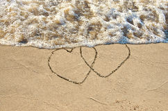Hearts in beach sand with surf Stock Image
