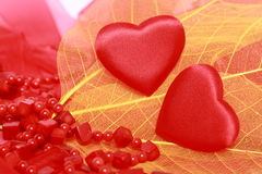 Hearts and beads. Red hearts and coral beads on leaves Royalty Free Stock Image