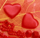 Hearts and beads on leaves. Red hearts and coral beads on leaves Royalty Free Stock Photos