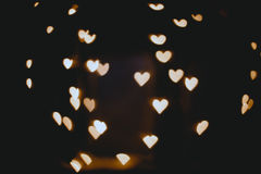 Hearts bokeh in dark texture for use in graphic design. Valentines style defocused lights background. St. Valentine`s Day Stock Photo