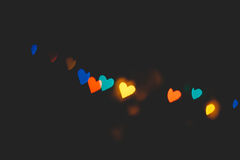 Hearts bokeh in dark texture for use in graphic design. Valentines style defocused lights background. St. Valentine`s Day Royalty Free Stock Photography