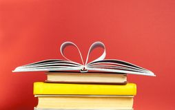 Hearts from book pages on red background.