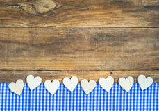 Hearts border on blue white checkered fabric and wooden board. Royalty Free Stock Photos