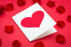 Hearts and a bouquet of red roses on red background, Valentines Day background. Red rose and paper hearts Valentines Day Stock Photo