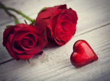 Hearts and a bouquet of red roses on wooden board Royalty Free Stock Photo