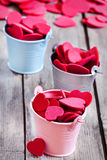 Hearts in buckets. Small colored buckets with red hearts on wooden table Stock Photography