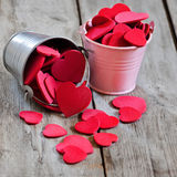 Hearts in buckets. Small colored buckets with red hearts on wooden table Stock Images