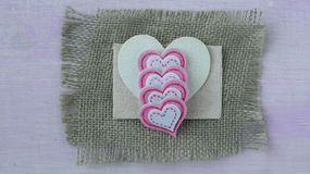Hearts with Burlap on Pink Wood Background Stock Photo