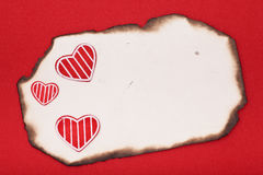 Hearts and burnt paper Stock Photos
