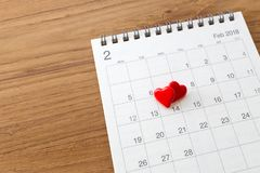 Hearts on calendar February 14. Valentines day on wooden table background royalty free stock images