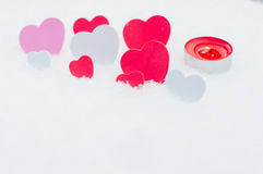 Hearts and candle on the snow. For Valentines Day Stock Photo
