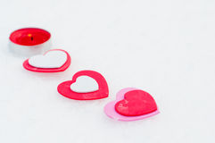 Hearts and candle on the snow. For valentines day Royalty Free Stock Photography