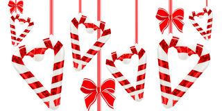 Hearts from candy canes and red bows. Over white Royalty Free Stock Photography