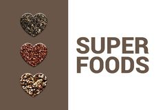 Hearts with chia seeds, red quinoa grains and blended quinoa on brown background. stock photos