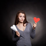 Hearts choice. Young girl with two hearts on black background Royalty Free Stock Photo
