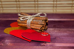 Hearts with cinnamon sticks and wedding ring on wooden planks St.Valentine's Day Stock Photo