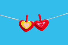 Hearts on clothesline with clothespins, blue background Royalty Free Stock Image