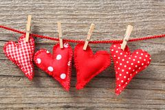 Hearts and clothespins on line. Handmade red cloth hearts hanging on a line by wood clothespins against a woodgrain textured wall Stock Photos