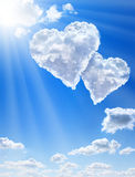 Hearts in clouds against a blue clean sky Stock Photo