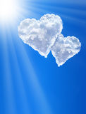 Hearts in clouds against a blue clean sky Royalty Free Stock Images