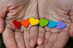 Hearts of the color of the rainbow in hands. Background of LGBT. Hearts of the color of the rainbow in women`s hands. Background of LGBT royalty free stock photography