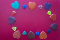 Hearts on dark pink background. Valentine`s Day postcard. Hearts of epoxy resin. Dark pink background. Valentine`s Day postcard Royalty Free Stock Photography