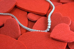 Hearts and diamonds. Red felt hearts and a diamond necklace stock photography